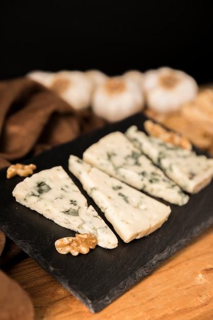 Fatias de queijo gorgonzola e noz na pedra preta Foto gratuita
