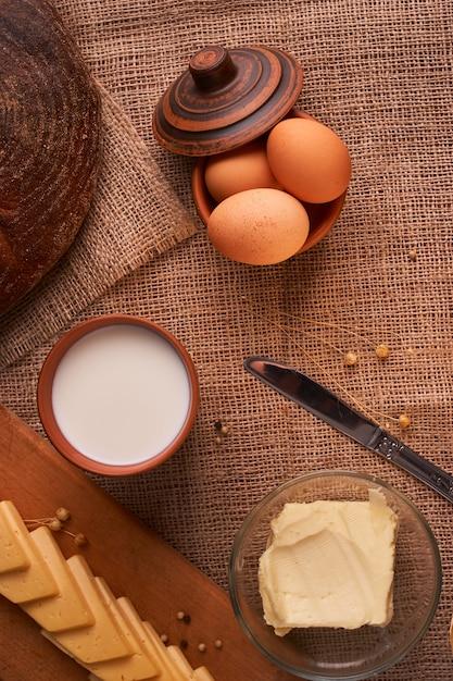 Fatias de queijo na mesa de madeira perto de baguete e leite Foto Premium