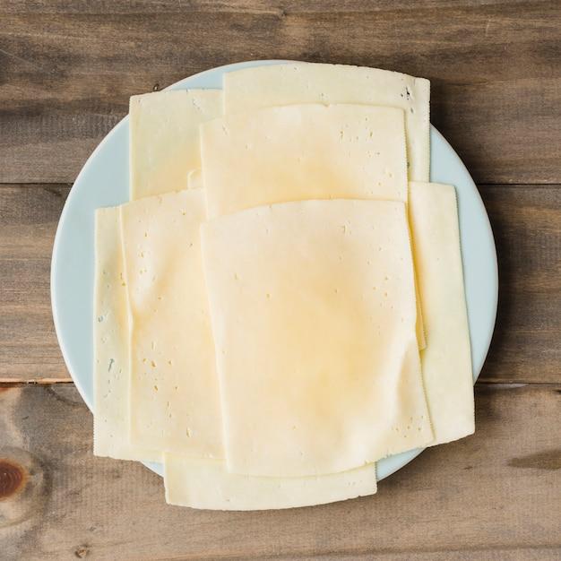 Fatias de queijo no prato branco contra o pano de fundo de prancha de madeira Foto gratuita