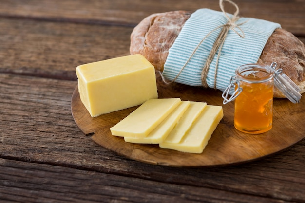 Fatias de queijo, pão e geléia de frutas na placa de madeira Foto Premium