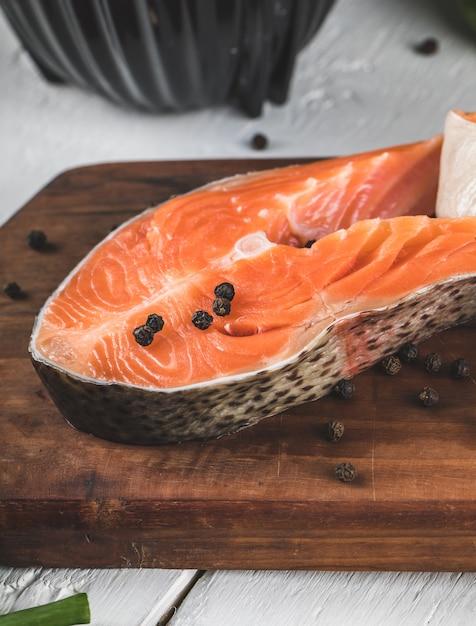 Fatias de salmão com bolas de pimenta preta em uma placa de madeira Foto gratuita