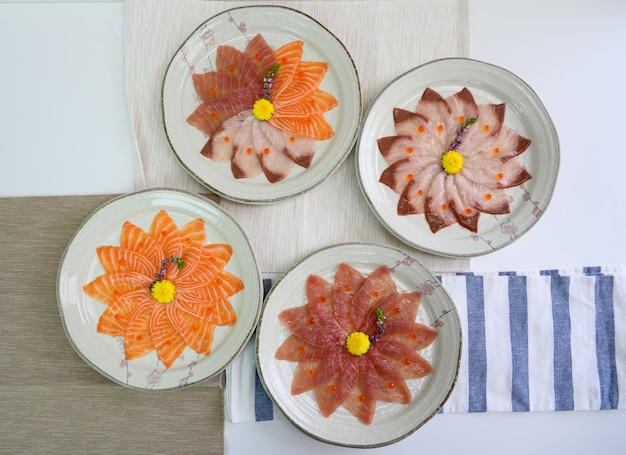 Fatias de salmão cru, hamachi, sashimi de maguro em prato de cerâmica Foto Premium