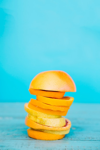Fatias empilhadas de frutas laranja e limão na superfície de madeira azul Foto gratuita
