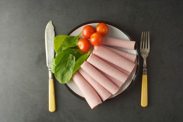 Fatias finas de presunto rolou no prato com legumes frescos Foto Premium