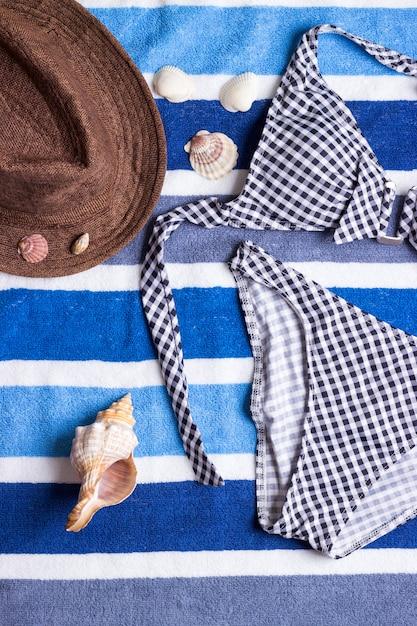 Fato de banho com acessórios de praia em fundo azul Foto Premium