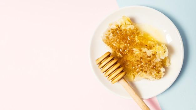 Favo de mel e dipper mel de madeira na placa em fundo duplo Foto gratuita