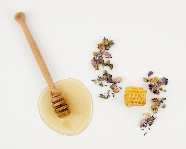 Favo de mel entre flores secas com concha de madeira Foto gratuita