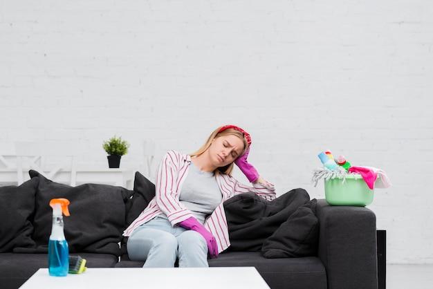 Faxineira no intervalo sentado no sofá Foto gratuita