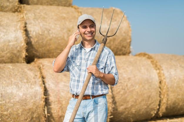 Fazendeiro de sorriso que fala no telefone quando no campo Foto Premium
