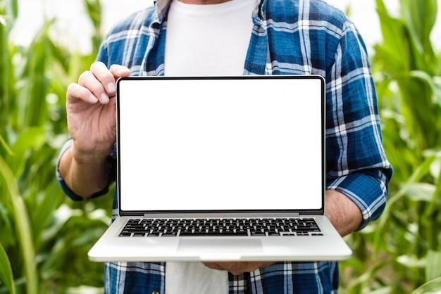 Fazendeiro que está em um portátil aberto terra arrendada do campo. maquete de tela branca Foto Premium