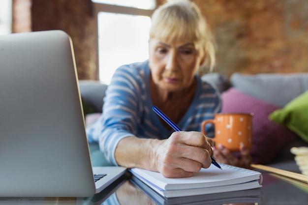 Fazendo anotações durante a aula. mulher sênior estudando em casa, fazendo cursos online Foto gratuita