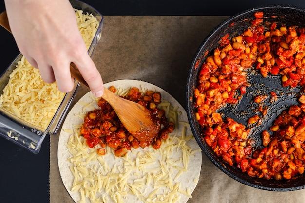 Fazendo de quesadilla, uma mulher espalha um recheio de uma frigideira em uma tortilha Foto Premium