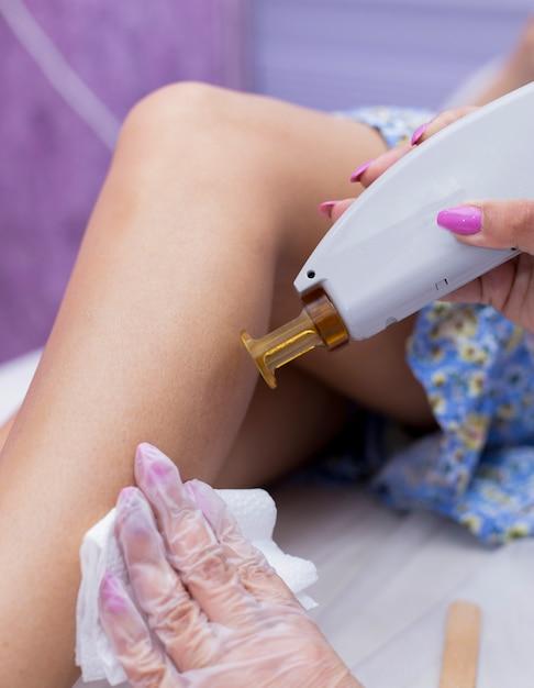 Fazendo depilação a laser na pele de pernas femininas. Foto gratuita