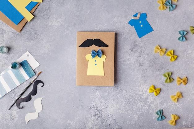 Fazendo o cartão para o dia dos pais. camisa com borboleta de macarrão. cartão de papel. bigode Foto Premium