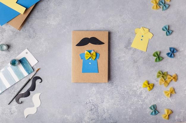 Fazendo o cartão para o dia dos pais. camisa com borboleta de macarrão. projeto de arte infantil. Foto Premium