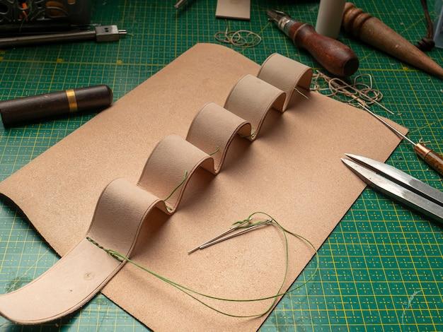 Fazendo um estojo de couro para baterias por um curtidor, em um tapete verde auto-cicatrizante, conceito de artesanato em couro Foto Premium