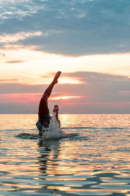 Fazendo um mergulho na água na praia. Foto Premium