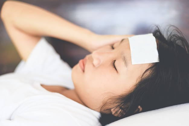 Febre criança com medição de temperatura de criança doente. criança com febre alta e deitado na cama mão segurando na testa. Foto Premium