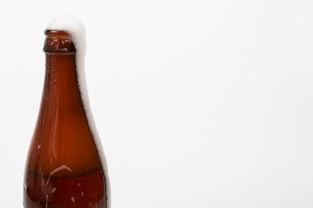 Fechar a garrafa de cerveja e espuma com espaço de cópia Foto gratuita