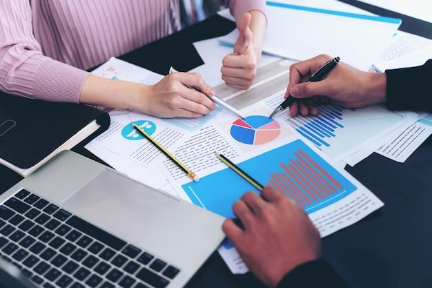 Fechar a mão do homem de negócios ocupado na mesa de escritório no notebook e documentos trabalhando Foto gratuita