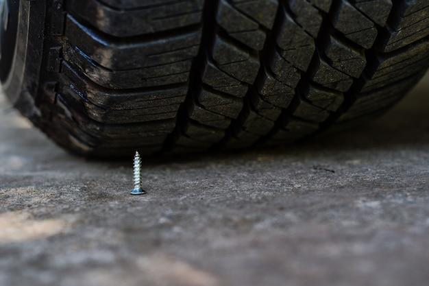 Fechar armadilha de parafuso foi colocado sob o pneu do carro Foto Premium