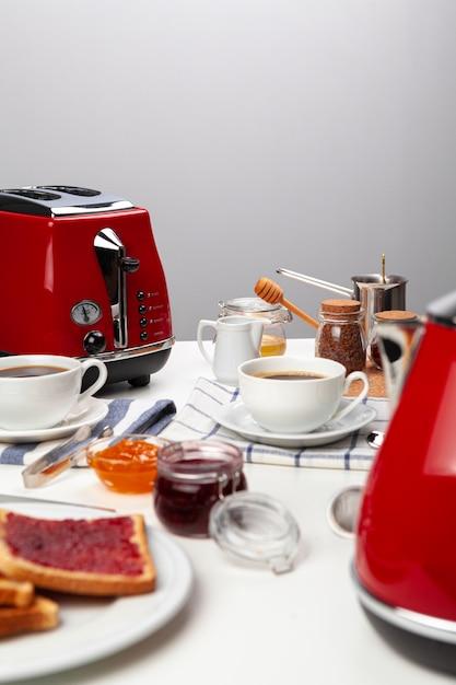Fechar foto da mesa da cozinha com eletrodomésticos, utensílios de cozinha com torradas e doces Foto Premium