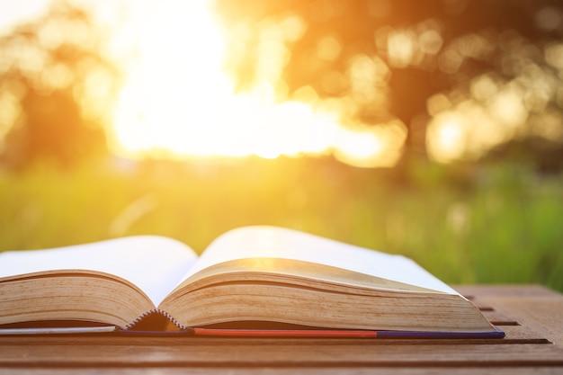 Fechar o livro na mesa em vez do sol Foto Premium