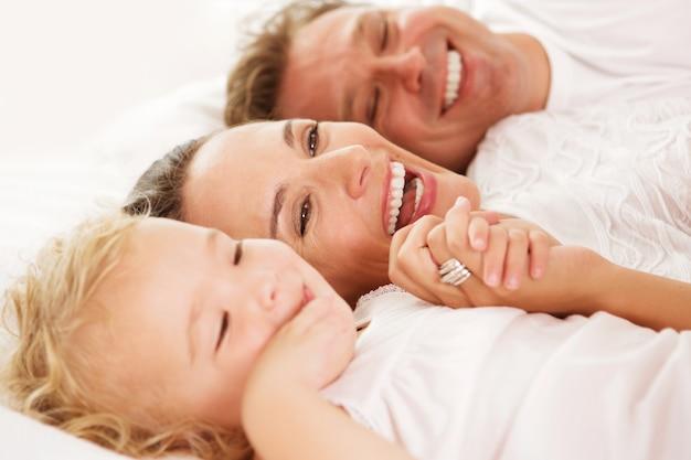 Fechar o retrato da menina bonitinha com os pais deitado na cama em casa e sorrindo Foto Premium
