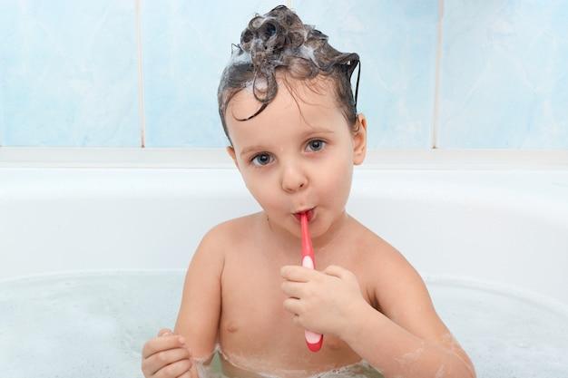 Fechar o retrato da menina carming, limpa os dentes com escova de dentes vermelha Foto gratuita