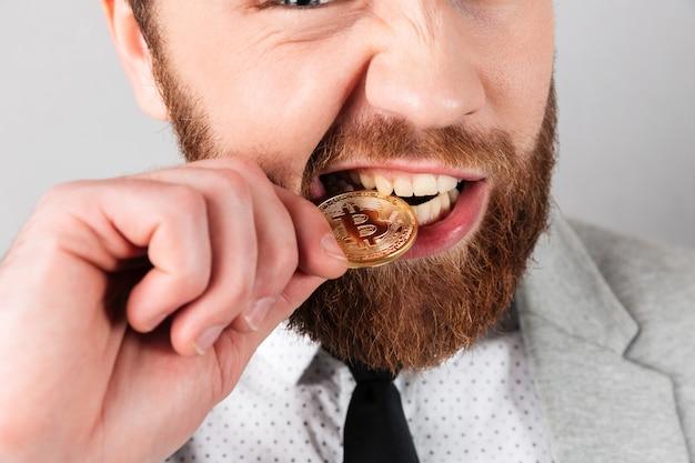 Fechar o retrato de um homem mordendo bitcoin dourado Foto gratuita