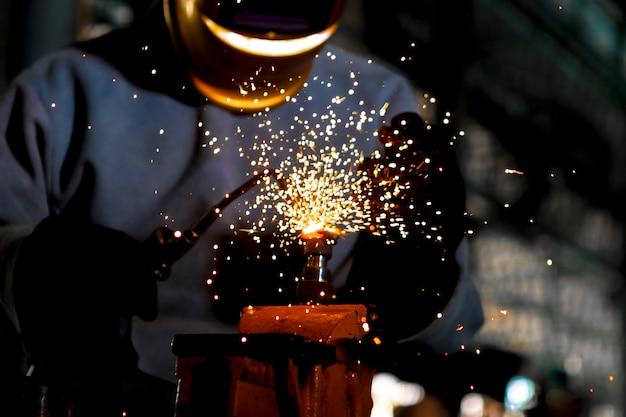 Fechar-se. aço de gás de trabalho do soldador do soldador do trabalhador na indústria com as luvas da máscara da segurança e o equipamento de segurança. Foto Premium
