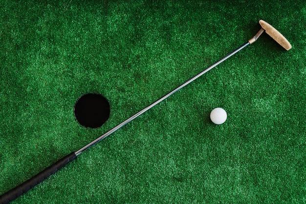 Fechar-se. clube de golfe e bola de golfe em um campo de minigolfe Foto Premium