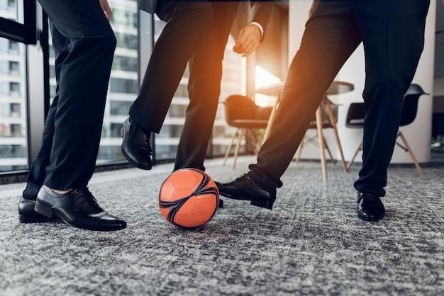 Fechar-se. homens em calças estritas e sapatos pretos jogam bola. Foto Premium