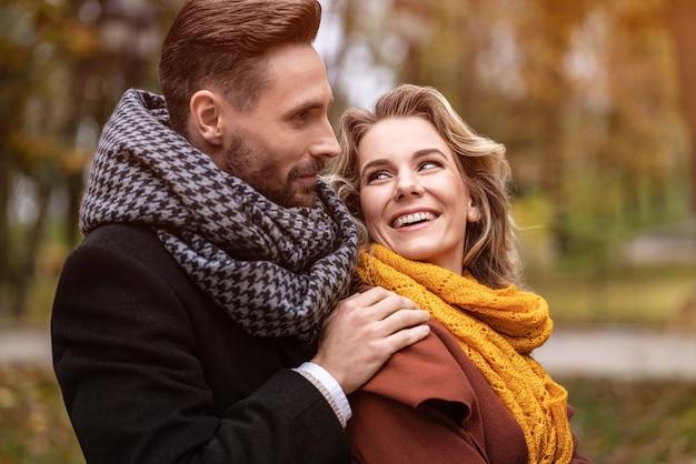 Fechar-se. jovens apaixonados, jovens, homem abraçando a mulher por trás quando ela olha para ele, feliz Foto Premium
