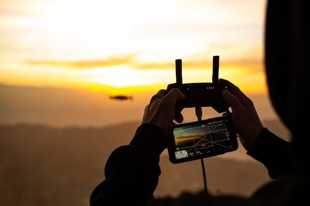 Fechar-se. um homem controla um drone ao sol do amanhecer no vulcão batur. bali, indonésia Foto gratuita