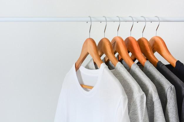 Feche a coleção de cor preta, cinza e branca (monocromática) pendurado no cabide de madeira Foto Premium