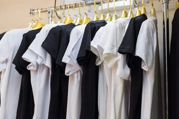 Feche a coleção de preto e branco monocromático, cabide de camisetas pendurado Foto gratuita
