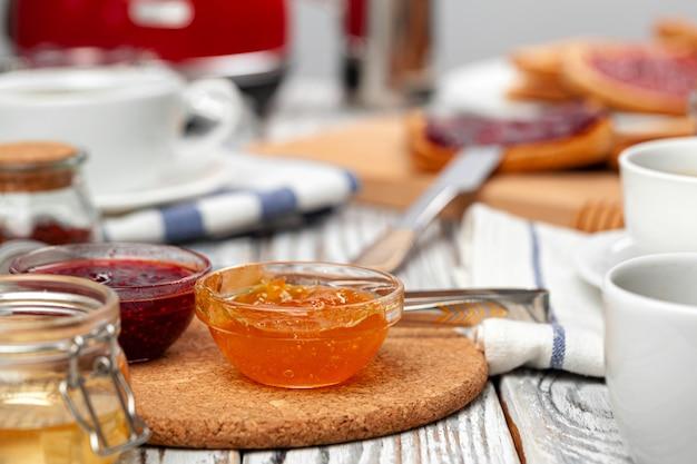 Feche a foto da mesa da cozinha com utensílios, utensílios de cozinha com torradas e doces Foto Premium