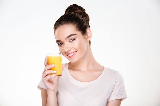 Feche a foto da mulher linda feliz bebendo suco de laranja doce de vidro transparente com sorriso Foto gratuita