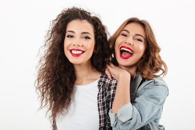 Feche a foto de duas meninas alegres posando juntos sobre parede branca Foto gratuita