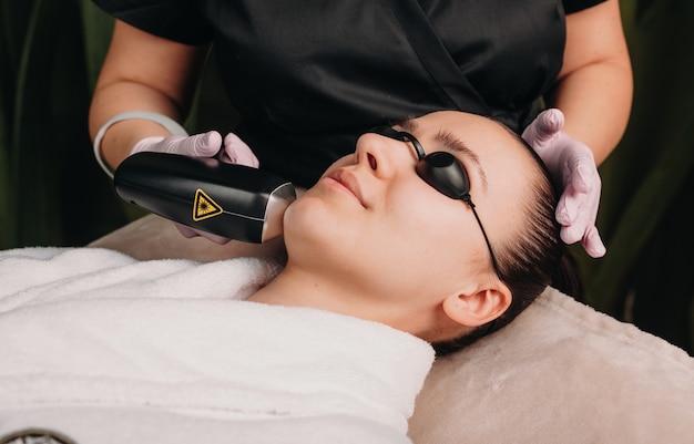Feche a foto de uma depilação facial com laser usando um dispositivo moderno em uma clínica de bem-estar Foto Premium