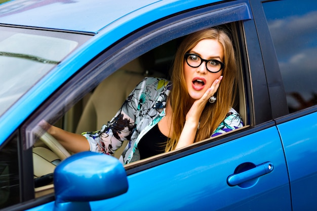 Feche a foto de viagens ao ar livre, estilo de vida, de mulher jovem loira hippie dirigindo carro, óculos e roupas brilhantes, grande sorriso, humor feliz, aproveite seu bom dia, jovem empresária. Foto gratuita