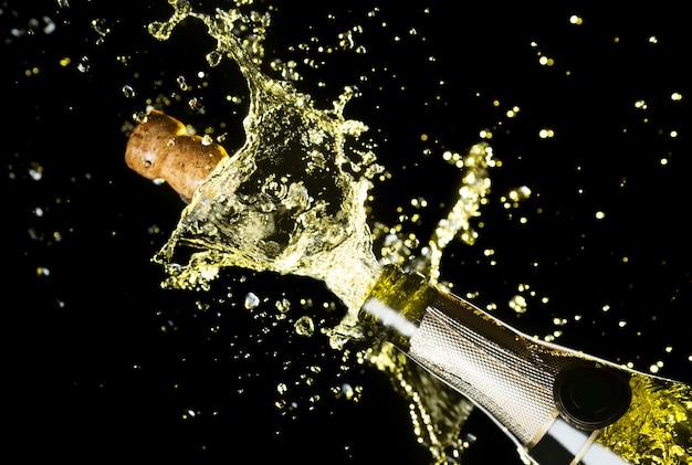 Feche a imagem da rolha de champanhe voando fora da garrafa de champanhe Foto Premium