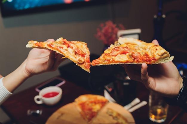 Feche a imagem de uma mulher com as mãos segurando uma fatia de pizza. Foto Premium