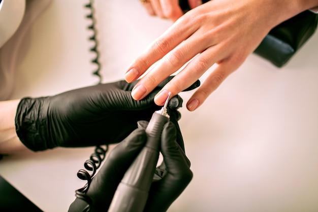 Feche a imagem de uma mulher fazendo manicure de hardware, indústria de manicure, detalhes de salão de beleza, mestre em manicure. Foto gratuita