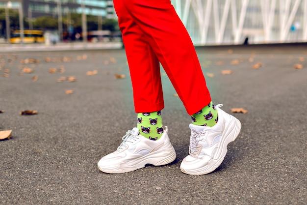 Feche a imagem de uma mulher hippie posando no outono, calças vermelhas, meias impressas na moda engraçadas e tênis grandes brancos. Foto gratuita