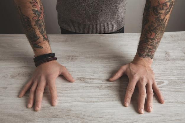 Feche a imagem detalhada de foco de irreconhecível homem brutal manga old school tatuado mãos no suéter cinza neutro na mesa de madeira branca, isolada. conceito de apresentação. Foto gratuita