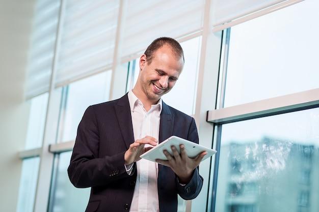Feche a imagem do homem de negócios, segurando um tablet digital, retrato de jovem bonito, trabalhando com o tablet no escritório. empresário inteligente e confidentes, segurando o touch pad com infográficos Foto Premium