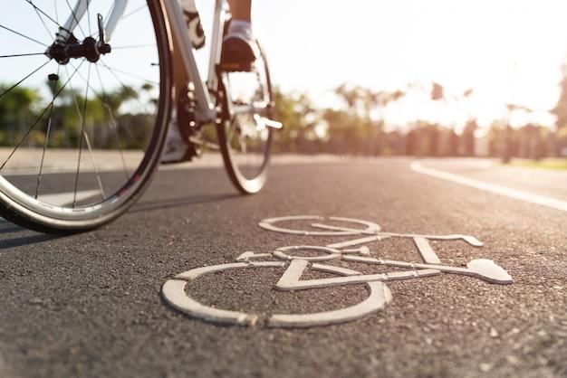 Feche a imagem do logotipo de ciclismo na estrada com pernas de ciclista de mulheres atléticas Foto Premium