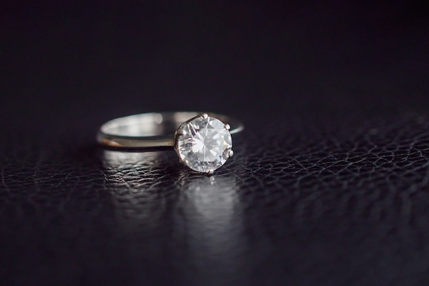 Feche a joia do anel de diamante na superfície de couro preto Foto Premium
